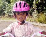 enfant casquée sur un vélo